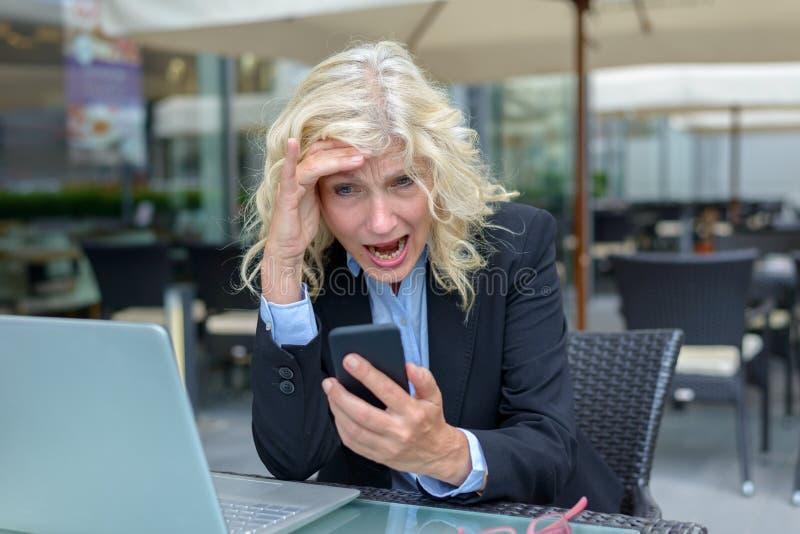 Mulher de negócios que reage no horror a seu móbil fotos de stock