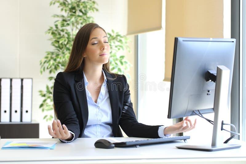 Mulher de negócios que relaxa fazendo a ioga no escritório imagens de stock royalty free