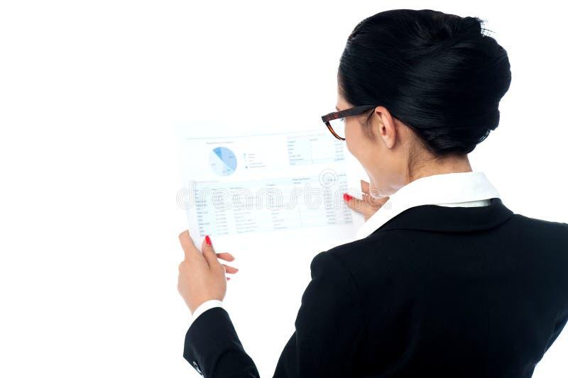 Mulher de negócios que revê o informe anual fotografia de stock royalty free