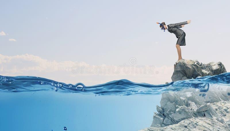A mulher de negócios que salta na água Meios mistos fotos de stock royalty free