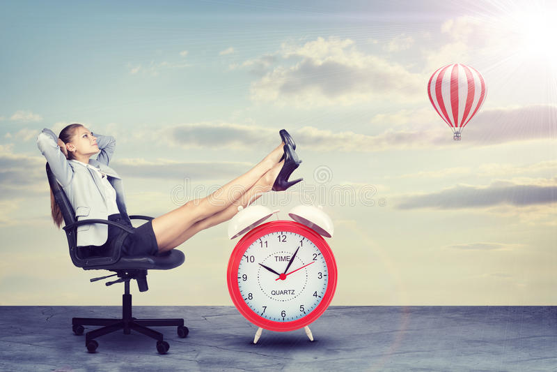 Mulher de negócios que senta-se com seus pés acima no alarme fotos de stock royalty free