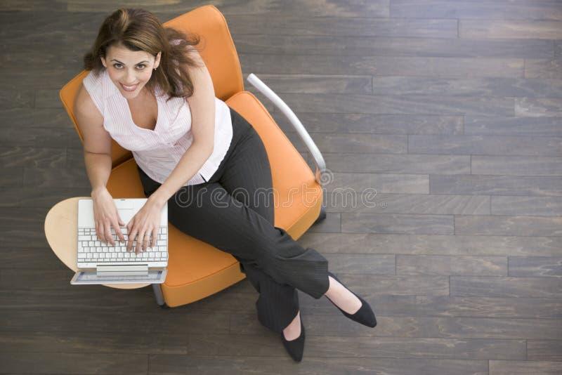 Mulher de negócios que senta-se dentro com sorriso do portátil fotos de stock royalty free