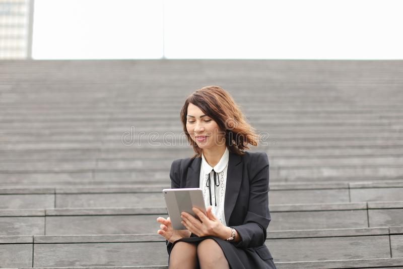 Mulher de negócios que senta-se em escadas com tabuleta e trabalho imagens de stock