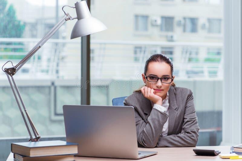 A mulher de negócios que senta-se em sua mesa no conceito do negócio foto de stock royalty free