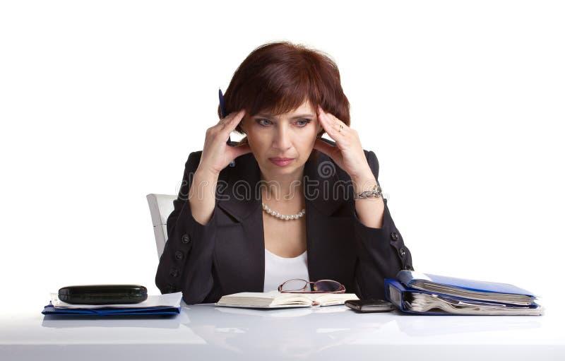 Mulher de negócios que senta-se em um cabelo da tabela e do rasgo fotografia de stock