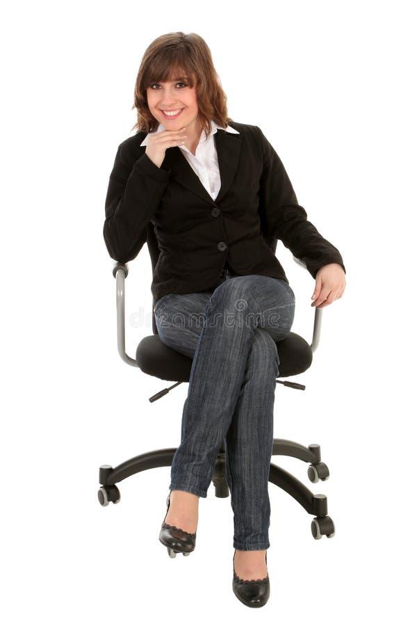 Mulher de negócios que senta-se na cadeira do escritório fotografia de stock royalty free