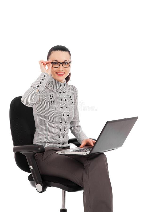 Mulher de negócios que senta-se na cadeira do escritório com portátil fotos de stock royalty free