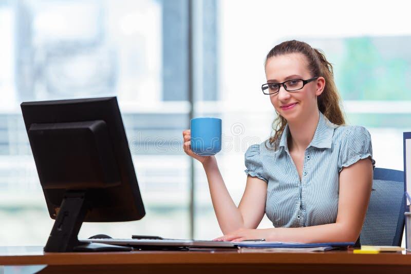 A mulher de negócios que senta-se na mesa de escritório fotos de stock