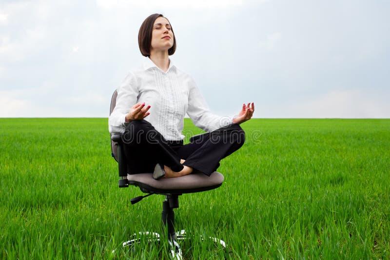 Mulher de negócios que senta-se na posição de lótus imagem de stock royalty free
