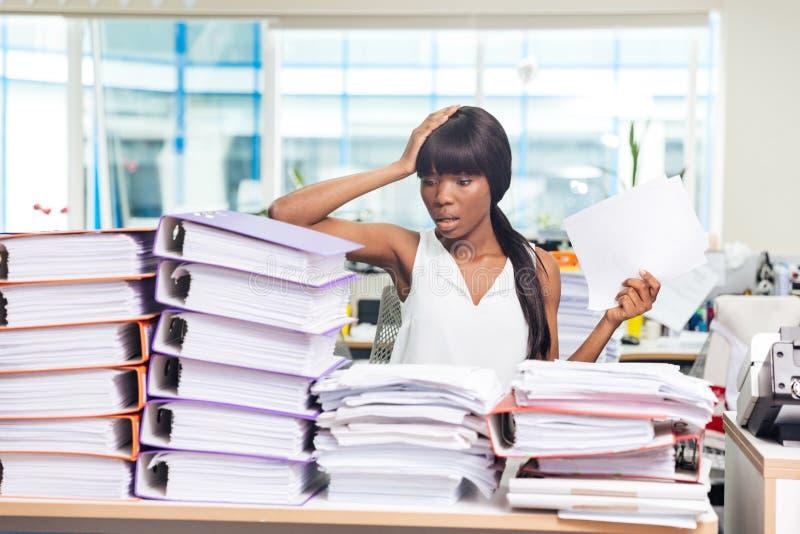 A mulher de negócios que senta-se na tabela com muitos forra imagens de stock