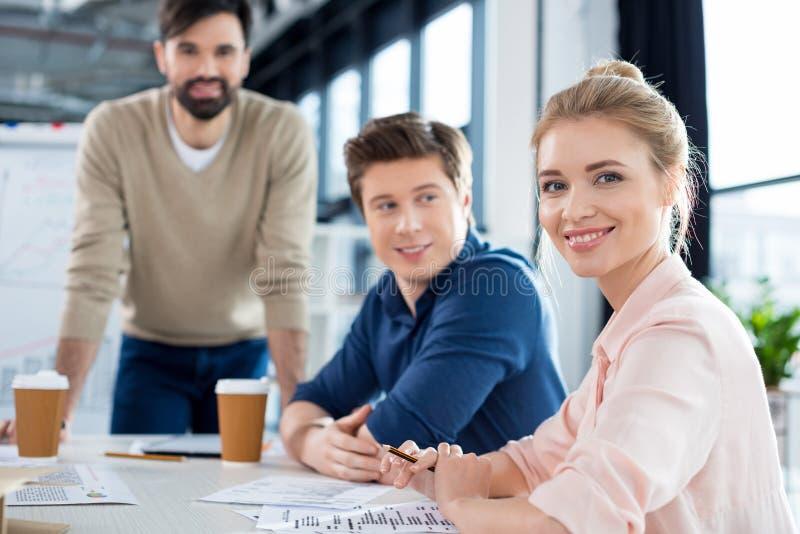 Mulher de negócios que senta-se na tabela com os colegas na reunião de negócios imagens de stock