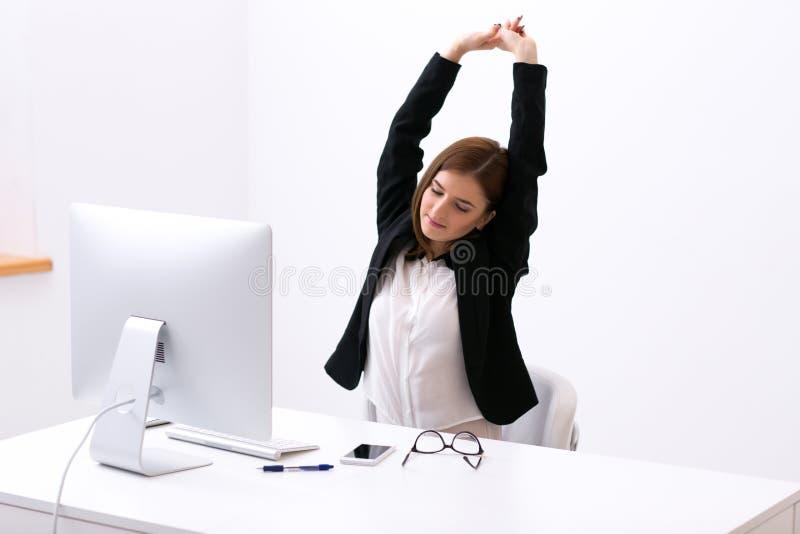 Mulher de negócios que senta-se na tabela no escritório fotos de stock