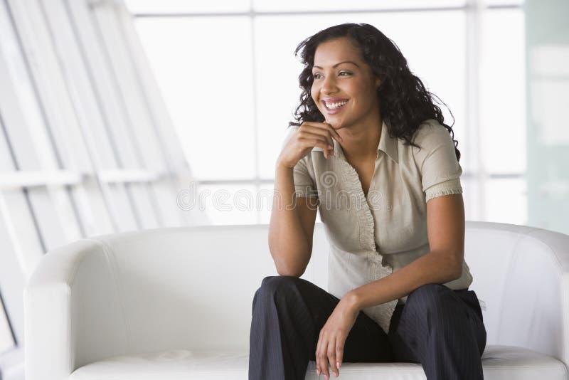 Mulher de negócios que senta-se no sofá na entrada fotos de stock royalty free
