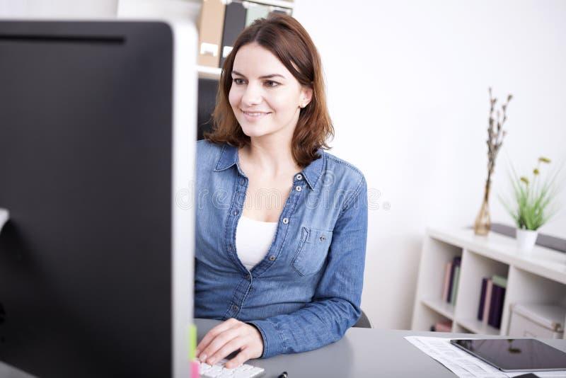 Mulher de negócios que sorri como trabalha em seu desktop imagens de stock