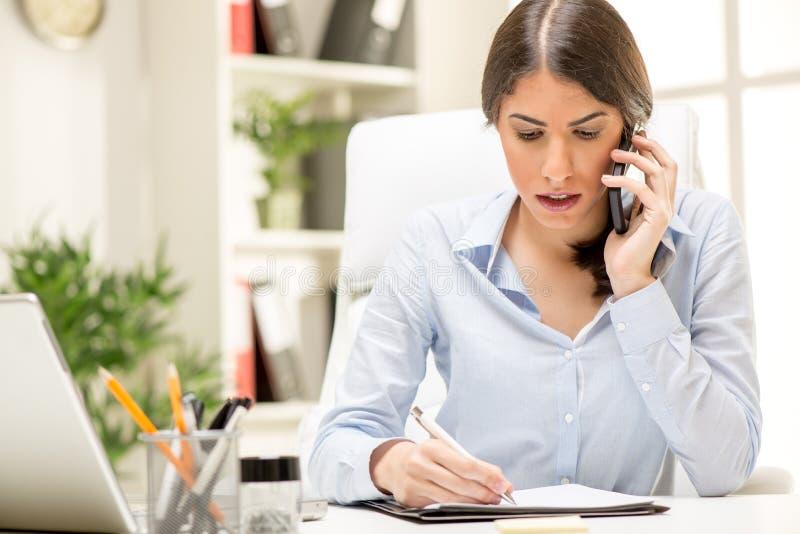Mulher de negócios que telefona no escritório foto de stock royalty free