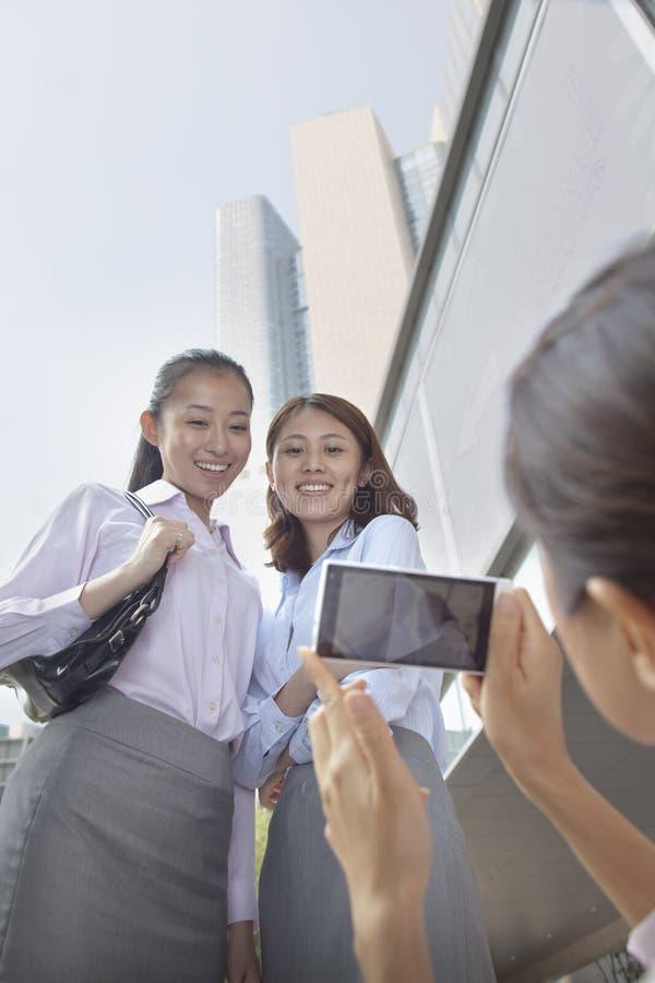 Mulher de negócios que toma a foto de seus colegas de trabalho com seu telefone celular fotos de stock royalty free