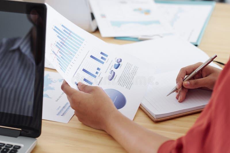 Mulher de negócios que trabalha com gráficos financeiros fotografia de stock