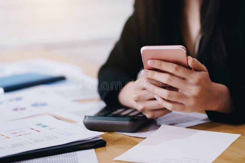 Mulher de neg?cios que trabalha com um telefone celular acima do contrato e da calculadora Conceito do neg?cio e da parceria fotos de stock royalty free