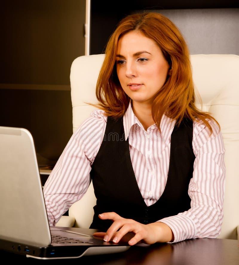 Mulher de negócios que trabalha em seu portátil foto de stock royalty free