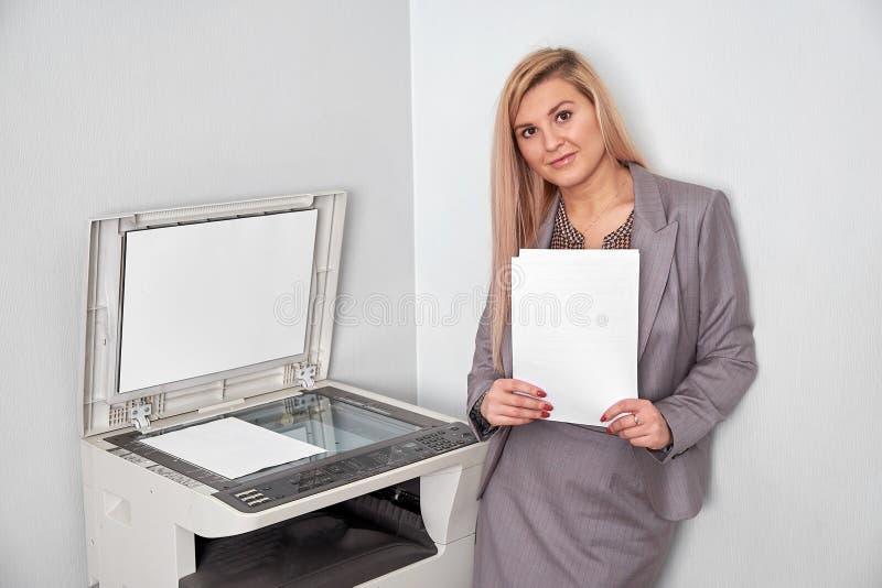 Mulher de negócios que trabalha em uma máquina da cópia no escritório imagens de stock royalty free