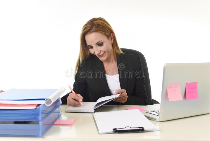 Mulher de negócios que trabalha na mesa de escritório do laptop que toma as notas que escrevem no caderno fotografia de stock royalty free