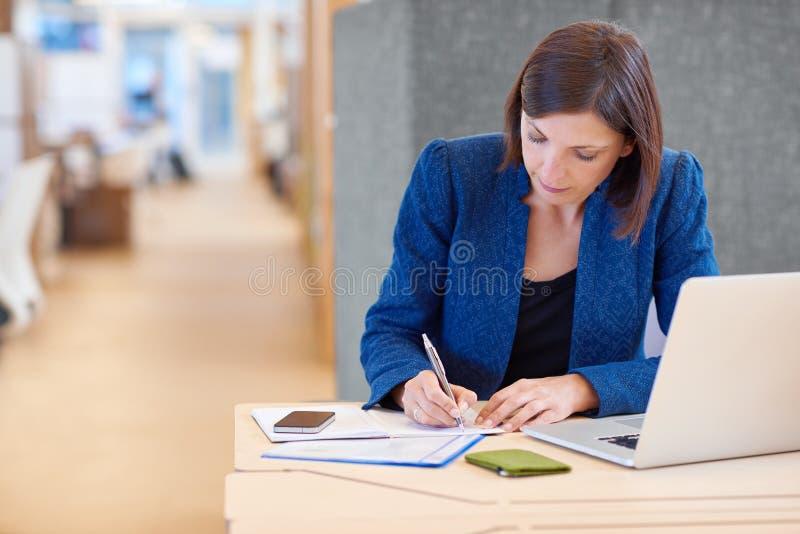 Mulher de negócios que trabalha no documento em sua mesa no escritório compartilhado fotografia de stock royalty free