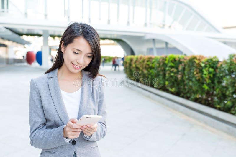 Mulher de negócios que trabalha no telefone celular em exterior imagens de stock