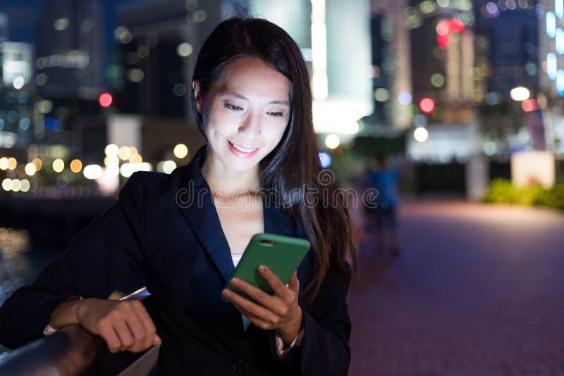 Mulher de negócios que trabalha no telefone celular na cidade na noite imagem de stock royalty free