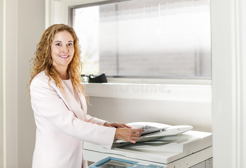 Mulher de negócios que usa a fotocopiadora no escritório fotos de stock