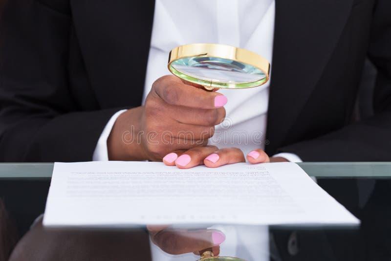 Mulher de negócios que usa a lupa para ler o original na mesa fotografia de stock