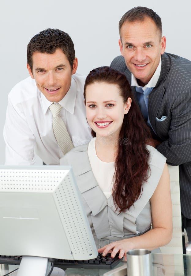 Mulher de negócios que usa o computador com seus colegas imagem de stock