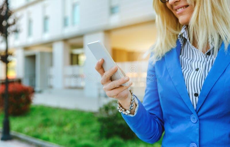 Mulher de negócios que usa o móbil na rua fotografia de stock
