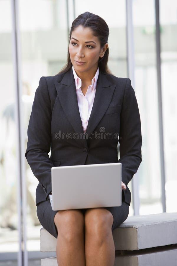 Mulher de negócios que usa o portátil fora foto de stock royalty free