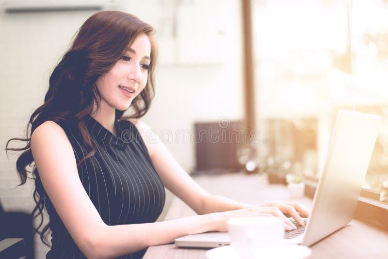 Mulher de negócios que usa o portátil na cafetaria na frente do espelho, funcionamento do negócio e para relaxar o conceito, a cr fotos de stock royalty free