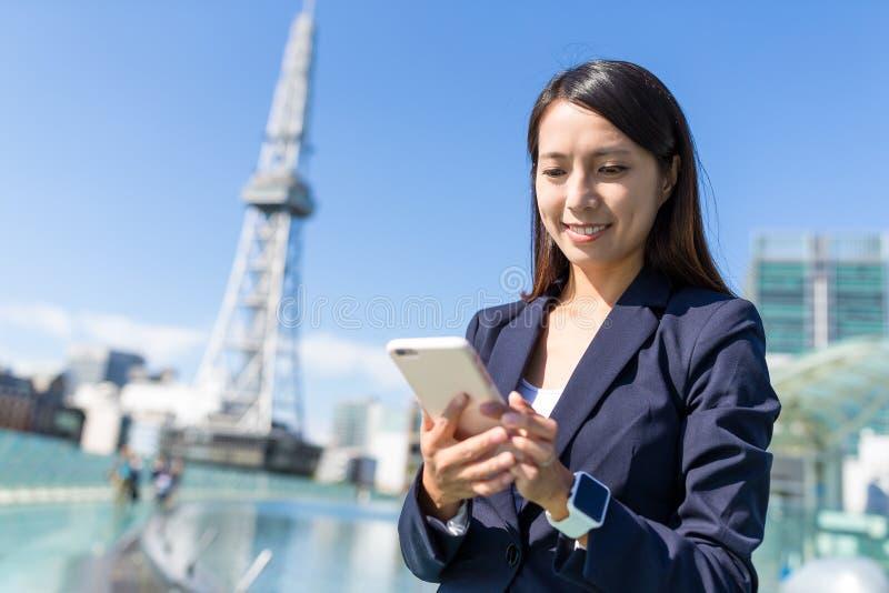 Mulher de negócios que usa o telefone celular na cidade de Nagoya imagem de stock