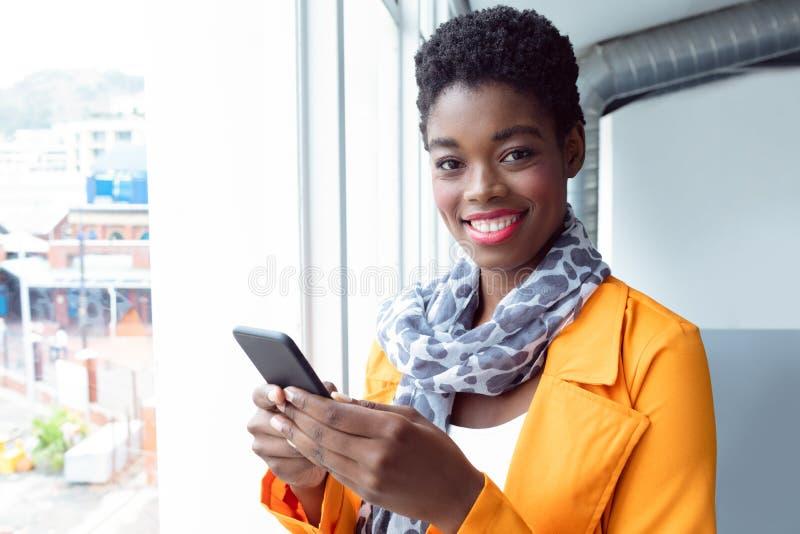 Mulher de negócios que usa o telefone celular perto da janela no escritório fotografia de stock