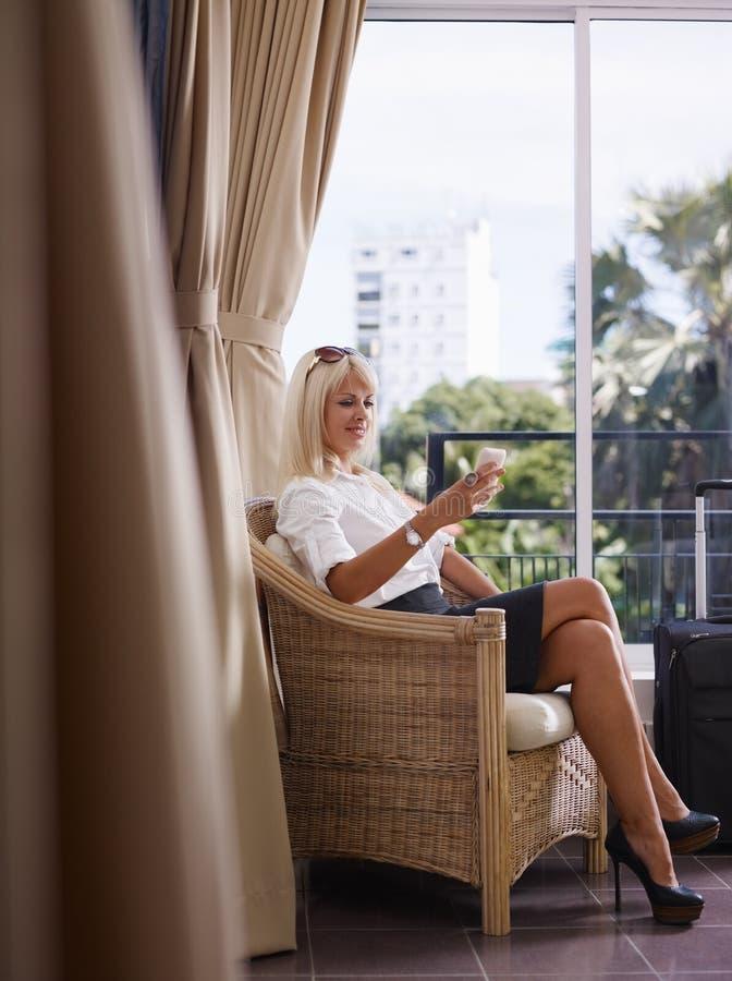 Mulher de negócios que usa o telefone móvel no quarto de hotel fotografia de stock