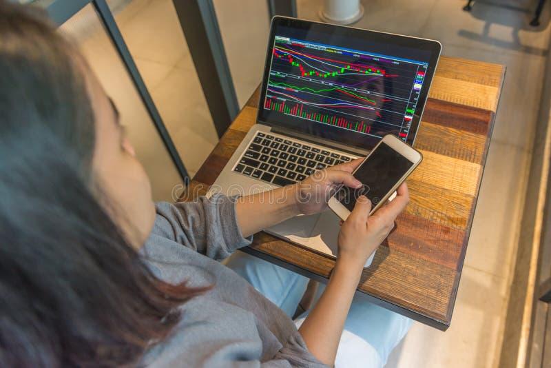 Mulher de negócios que usa o telefone para trocar no mercado de valores de ação imagem de stock royalty free