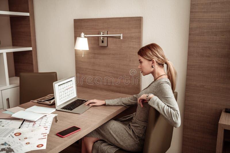 Mulher de negócios que usa seu portátil ao olhar a programação fotografia de stock