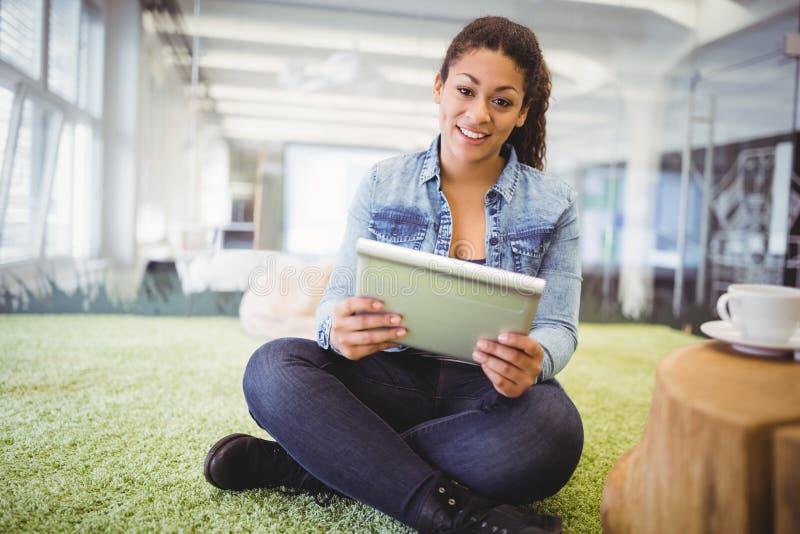 Mulher de negócios que usa a tabuleta digital ao sentar-se no tapete no escritório imagens de stock royalty free