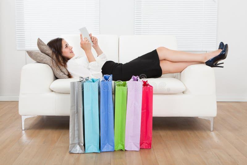 Mulher de negócios que usa a tabuleta digital com os sacos de compras no assoalho imagens de stock