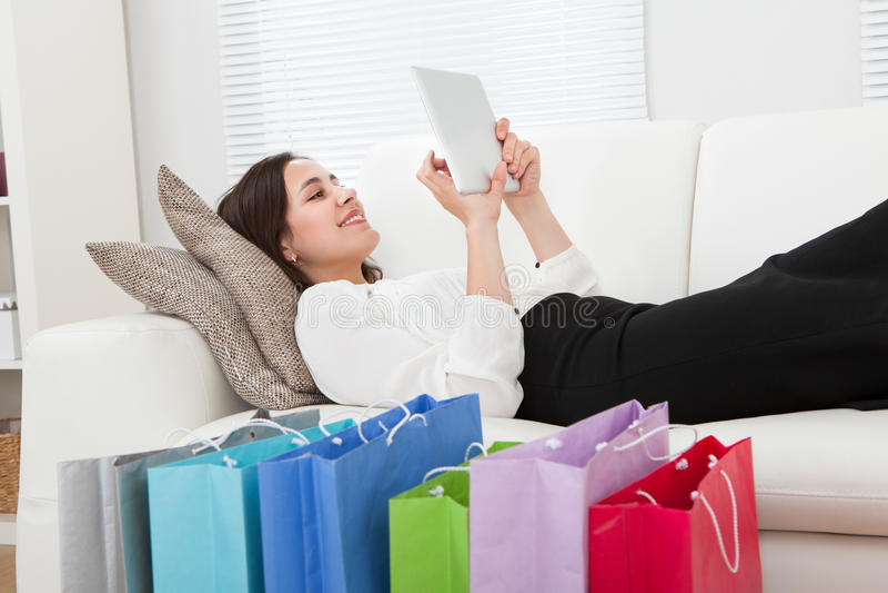 Mulher de negócios que usa a tabuleta digital com os sacos de compras no assoalho imagens de stock royalty free