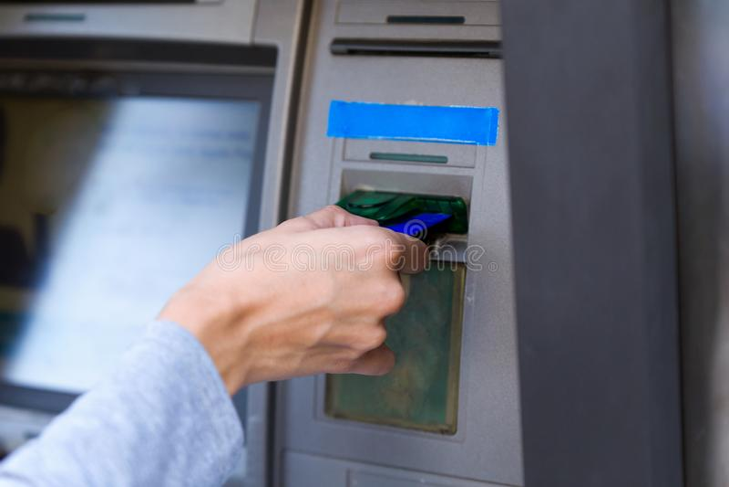 Mulher de negócios que usa um cartão de crédito para retirar o dinheiro em um ponto do dinheiro do banco na rua fotografia de stock royalty free