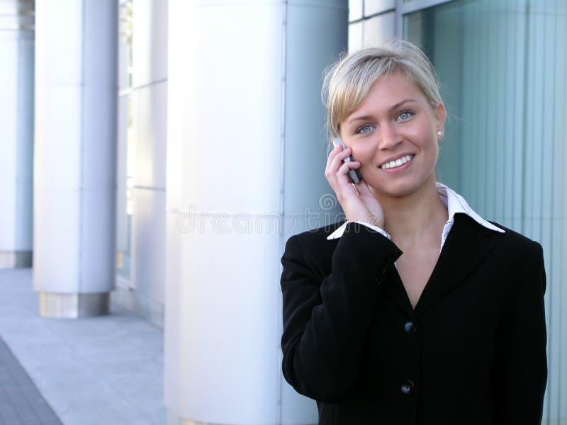 Mulher de negócios que usa um telefone móvel fotografia de stock