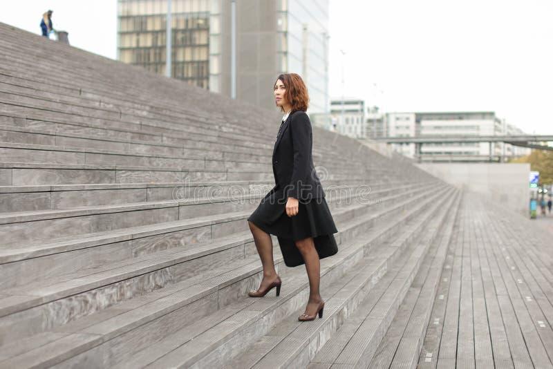 Mulher de negócios que vai acima em escadas no fundo alto das construções fotografia de stock