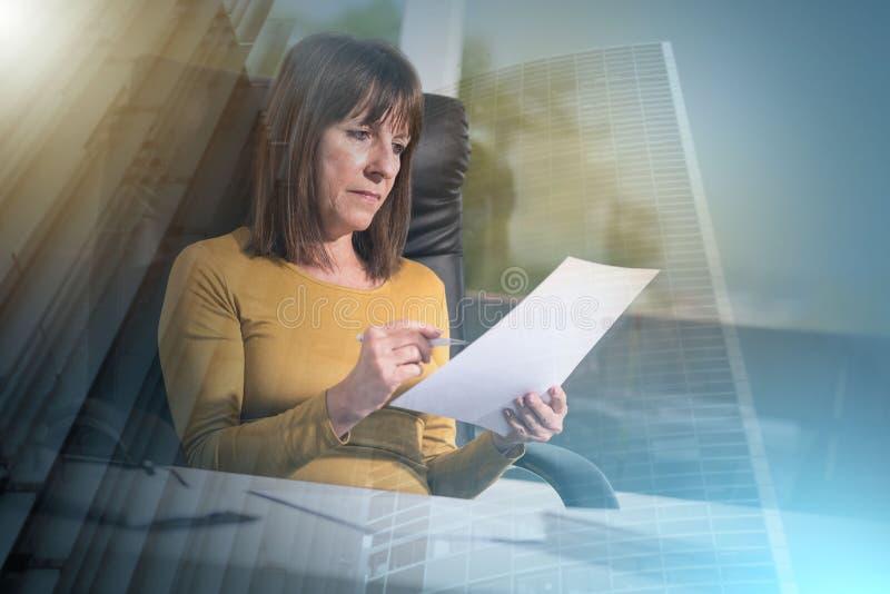 Mulher de negócios que verifica o documento, efeito da luz; exposição múltipla foto de stock