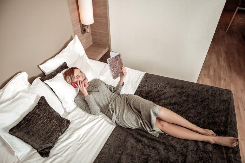 Mulher de negócios que verifica sua programação ao encontrar-se na cama fotografia de stock