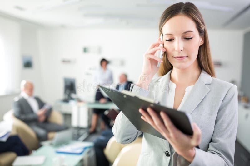 Mulher de negócios Reading Clipboard While que usa Smartphone no escritório foto de stock