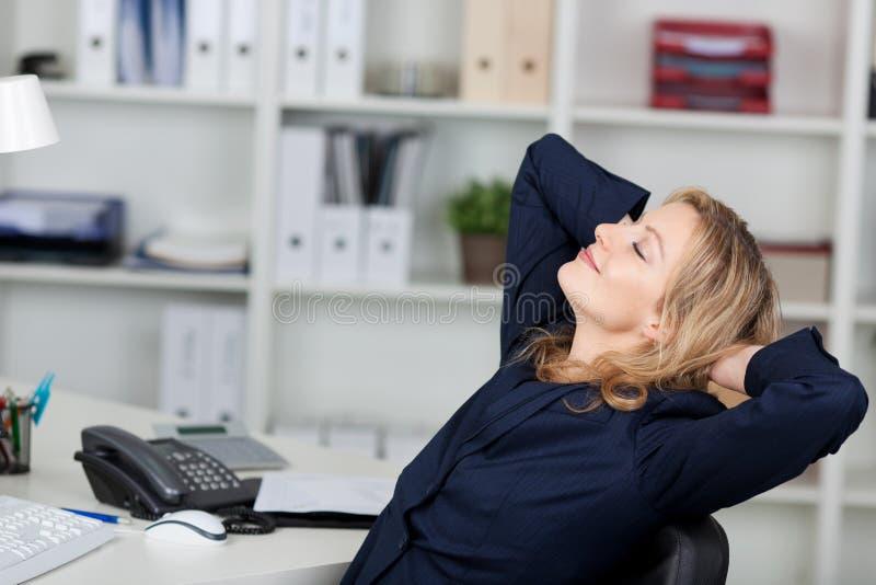 Mulher de negócios Relaxing With Hands atrás da cabeça fotografia de stock