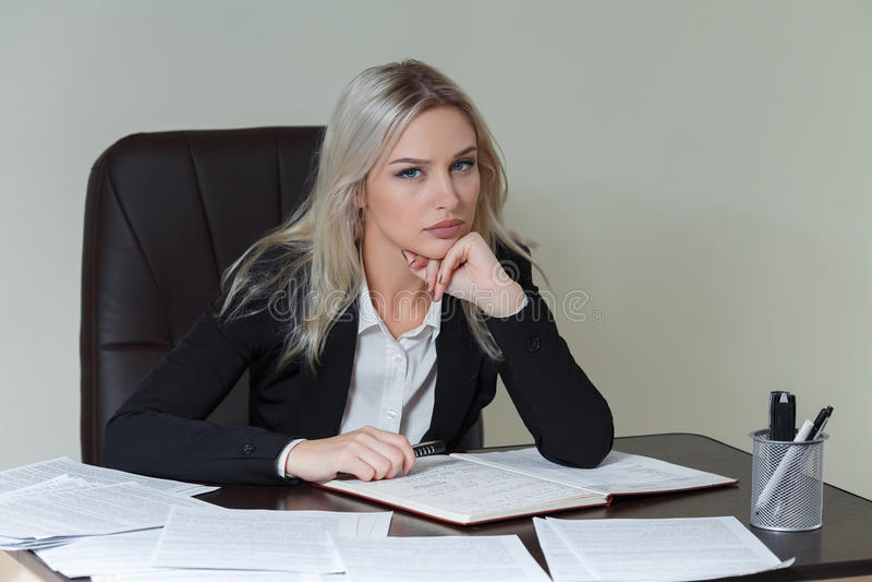 mulher de negócios restrita no terno que senta-se na tabela com originais imagens de stock